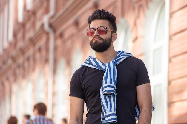 Retrato de cara alegre positivo elegante estudante de óculos com um bigode e barba ao ar livre. o conceito de pessoas alegres de sucesso.