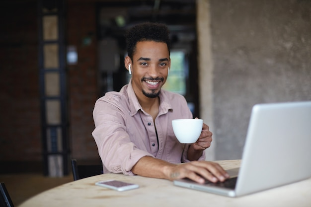 Retrato de cara barbudo de pele escura positiva em uma camisa bege posando sobre um escritório moderno com uma xícara de chá na mão erguida, olhando para a câmera com alegria e segurando a mão em seu laptop