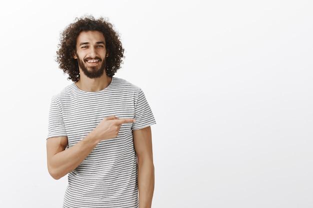 Retrato de cara bonito com sorriso encantador e cabelos cacheados em roupas casuais, apontando para a direita e sorrindo com expressão assegurada