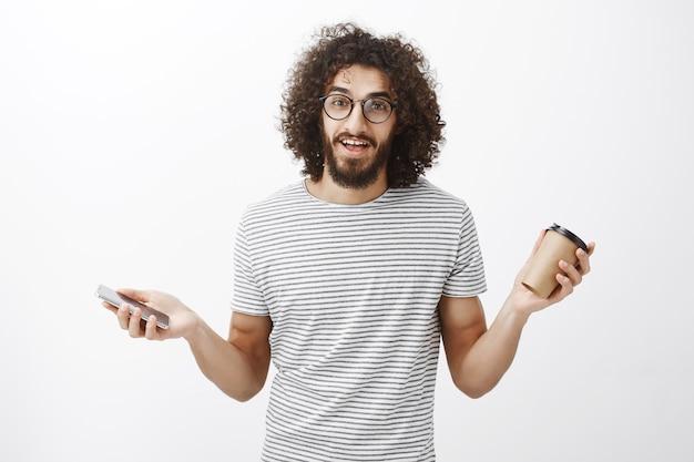 Retrato de cara despreocupado, amigável e bonito de óculos e camisa listrada, estendendo as mãos com uma xícara de café e smartphone, falando apaixonadamente sobre o novo jogo