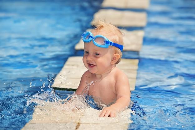 Retrato de cara engraçada de menino na piscina.