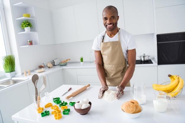 Retrato de cara fazendo torta de pizza saborosa e saborosa com produtos saudáveis em uma cozinha moderna dentro de casa
