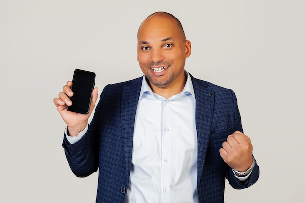 Retrato de cara feliz jovem empresário afro-americano, mostra a tela do smartphone, grita com orgulho e comemora vitória e sucesso, muito animado, alegra-se nas emoções.