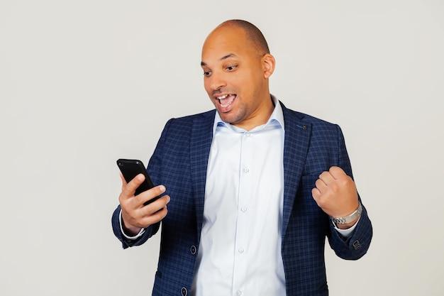 Retrato de cara feliz jovem empresário afro-americano usando telefone inteligente, gritando com orgulho e comemorando a vitória e o sucesso, emoções muito animado, regozijando-se.