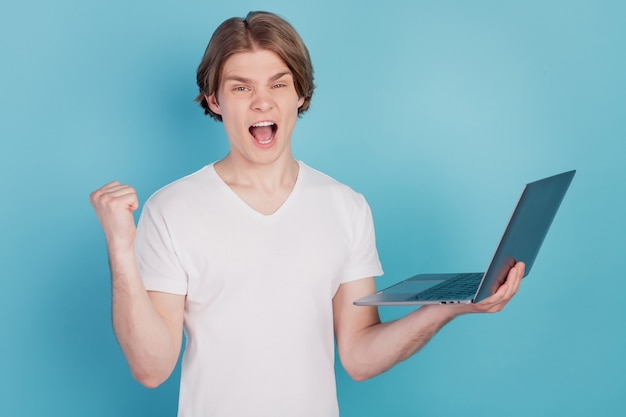 Retrato de cara inteligente segurando laptop levanta punho triunfante isolado sobre fundo azul