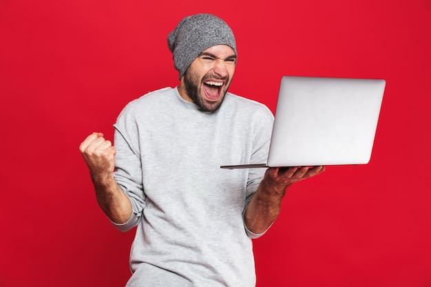 Retrato de cara otimista dos 30 anos em roupa casual se regozijando enquanto segura um laptop prateado isolado