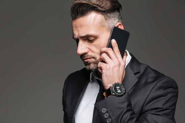 Retrato de cara profissional em terno preto, falando no smartphone com relógio no pulso, isolado sobre cinza escuro