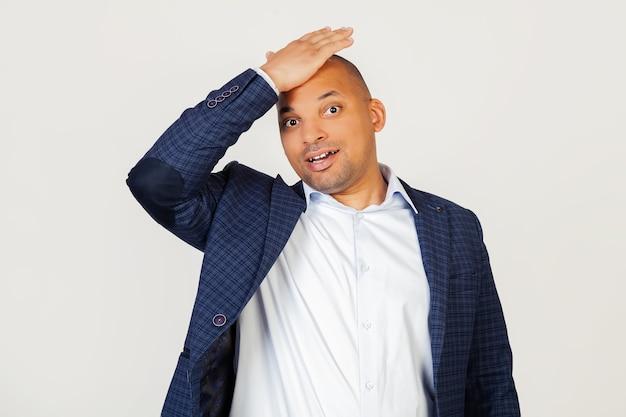 Retrato de cara surpreso do jovem empresário afro-americano, descansando a mão na cabeça por engano, lembre-se do erro conceito de memória ruim, esquecido.