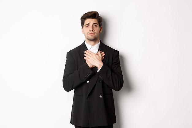 Retrato de cara tocado e compassivo de terno, segurando o coração de mãos dadas e olhando com pena para a câmera, em pé sobre um fundo branco