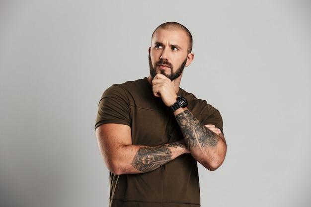 Retrato de careca viril com tatuagem nos braços, olhando de lado e segurando o queixo, isolado sobre parede cinza