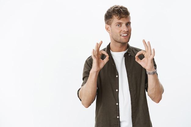 Retrato de carismático assertivo e simpático loiro masculino bonito com olhos azuis sorrindo e mostrando gestos ok em confirmação, recomendando o melhor lugar para se divertir