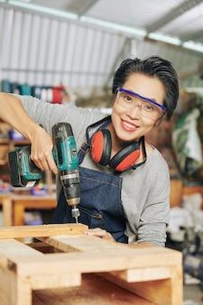 Retrato de carpinteiro feliz em óculos de proteção, usando furadeira ao fazer móveis de madeira na oficina