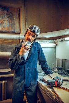 Retrato de carpinteiro sério em seu local de trabalho.