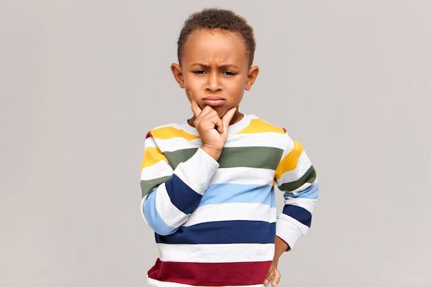 Retrato de carrancudo garotinho de pele escura mal-humorado expressando relutância ou desacordo. criança africana séria em um macacão elegante segurando a mão em seu queixo, com olhar pensativo e frustrado