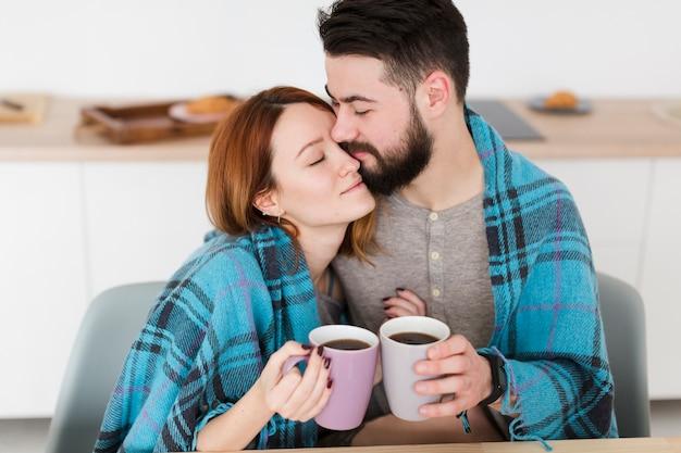 Retrato de casal abraçando e segurando cafés