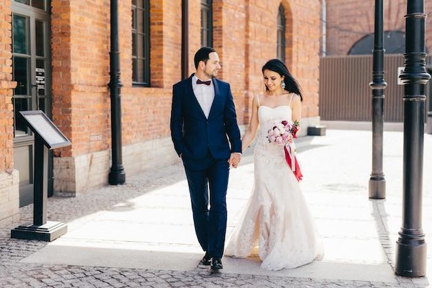 Retrato de casal adorável afetuoso, mantém as mãos juntas, caminhar ao ar livre