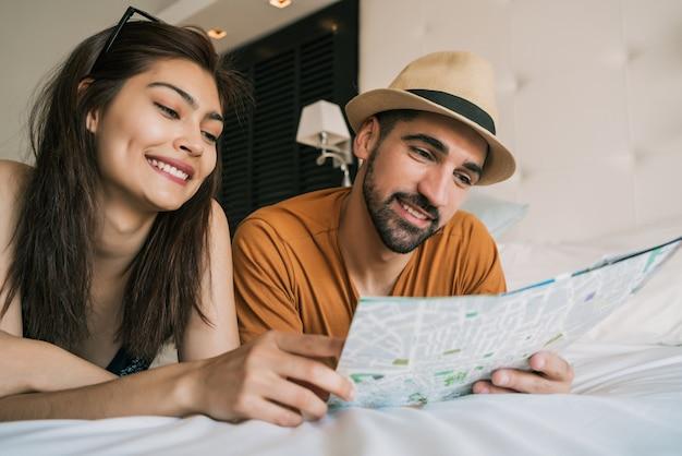 Retrato de casal adorável organizando sua viagem com um laptop no quarto do hotel
