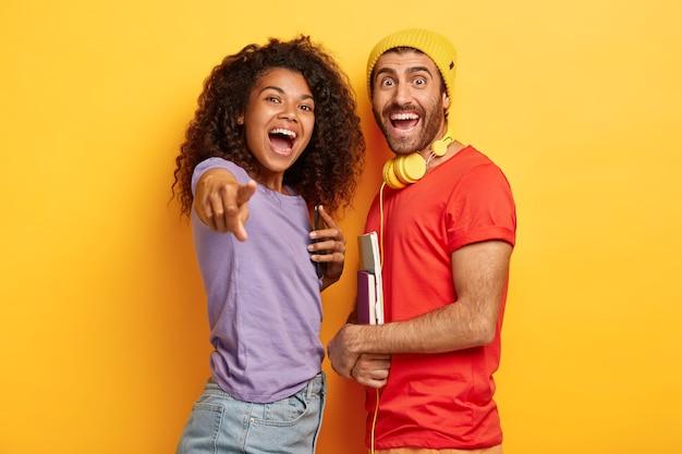 Retrato de casal alegre e elegante posando contra a parede amarela com gadgets