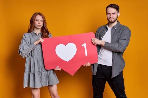 Retrato de casal alegre em traje de festa segurando um ícone em forma de coração, recomendando clicar no botão da mídia social