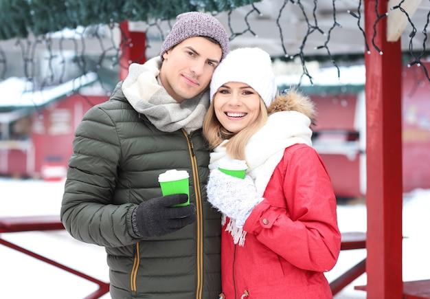 Retrato de casal amoroso feliz bebendo café ao ar livre num dia de inverno