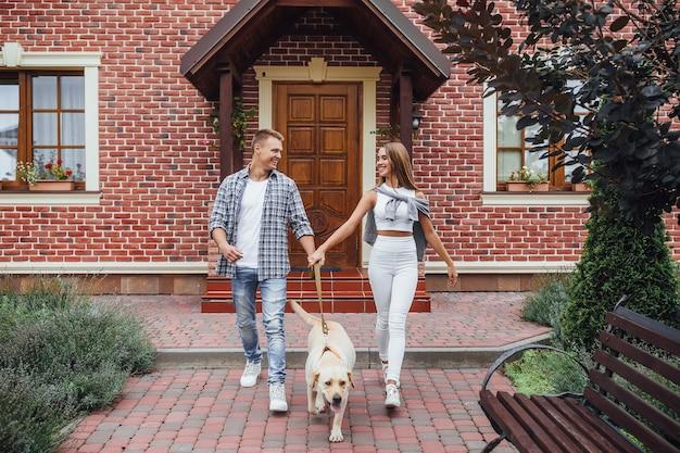 Retrato de casal animado do lado de fora da nova casa com o cachorro.