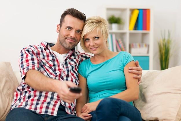 Retrato de casal apaixonado assistindo tv