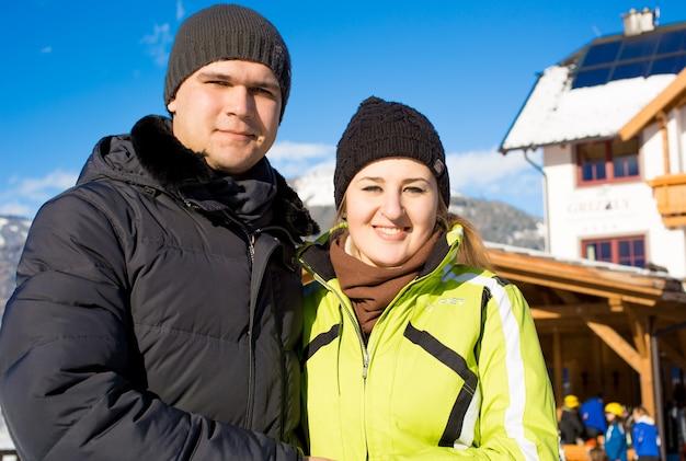 Retrato de casal apaixonado e sorridente posando contra uma estação de esqui de inverno