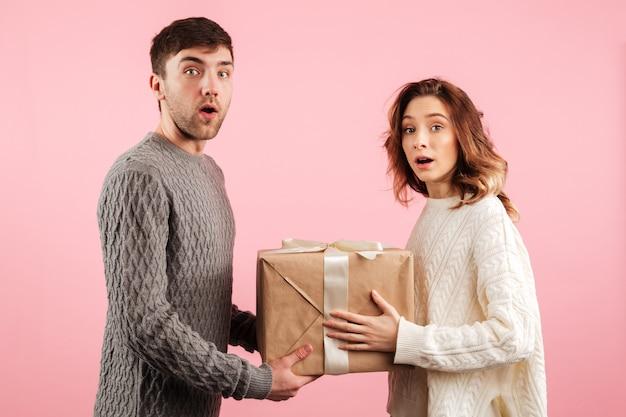 Retrato de casal apaixonado surpreso, vestido de camisolas