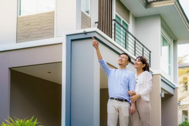 Retrato de casal asiático caminhando abraçando e apontando juntos, parecendo feliz na frente de sua nova casa para começar uma nova vida.