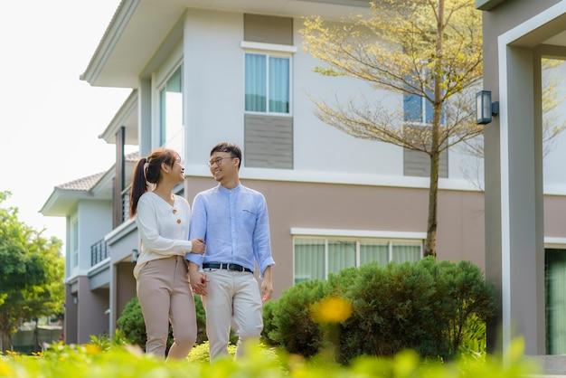 Retrato de casal asiático caminhando e se abraçando, parecendo feliz na frente de sua nova casa para começar uma nova vida.