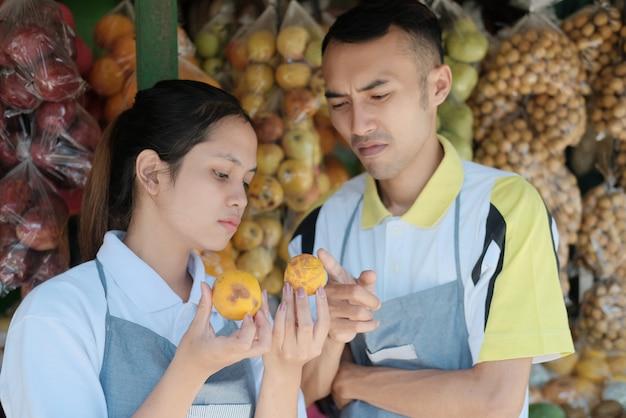 Retrato de casal assistente de loja escolhendo frutas cítricas enquanto classifica frutas em uma barraca de frutas no