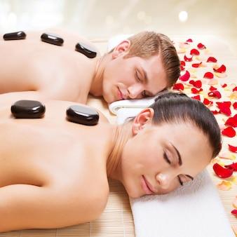 Retrato de casal atraente relaxante no salão spa com pedras quentes no corpo.