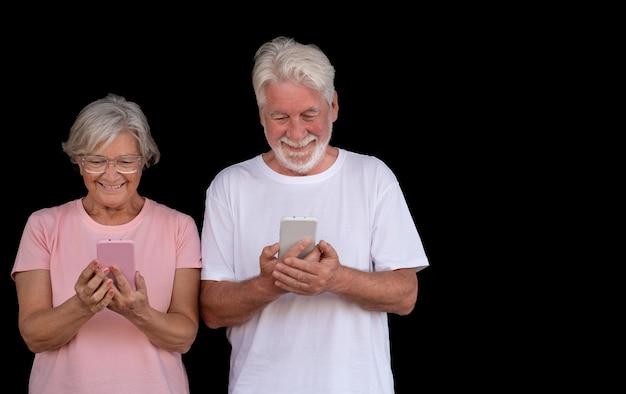 Retrato de casal atraente sênior usando telefones celulares. aposentado idoso desfrutando de social e tecnologia. fundo preto