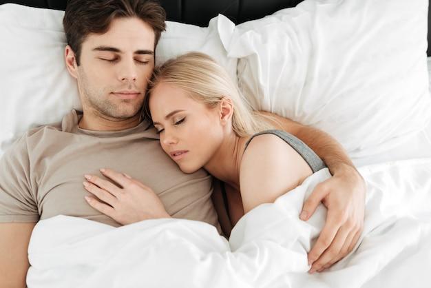Retrato de casal bonito calmo, dormindo na cama