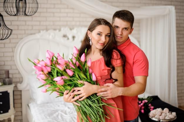 Retrato de casal bonito e jovem com grande buquê de tulipas cor de rosa