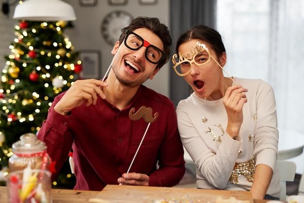 Retrato de casal brincalhão com máscaras de natal