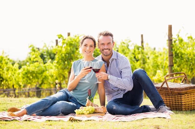 Retrato de casal brindando o copo de vinho no gramado