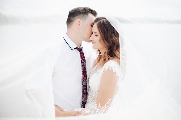 Retrato de casal caucasiano de recém-casados se abraçando e beijando junto com um véu de noiva ao redor deles