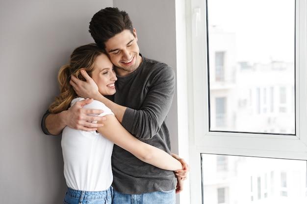 Retrato de casal caucasiano sorrindo e se abraçando em pé perto de uma grande janela em uma sala iluminada em casa
