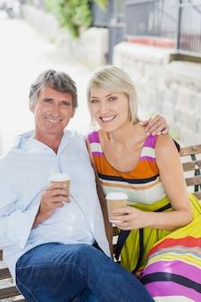 Retrato de casal com café no banco