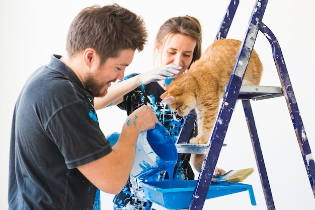 Retrato de casal com gato despejando tinta