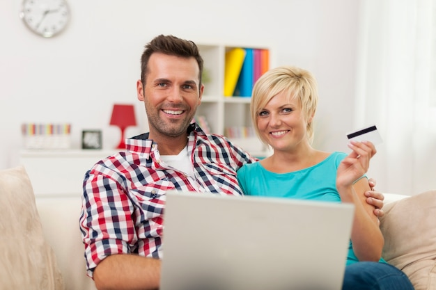 Retrato de casal com laptop e cartão de crédito em casa