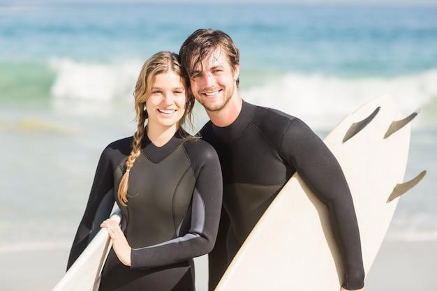 Retrato de casal com pé de prancha de surf na praia