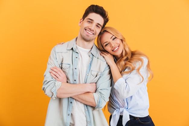 Retrato de casal contente em roupas básicas, sorrindo enquanto uma mulher coloca a cabeça no ombro masculino, isolado sobre a parede amarela