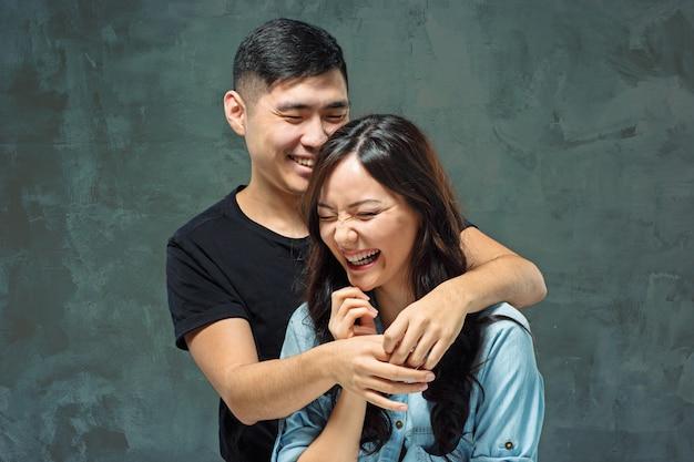 Retrato de casal coreano sorridente em um cinza