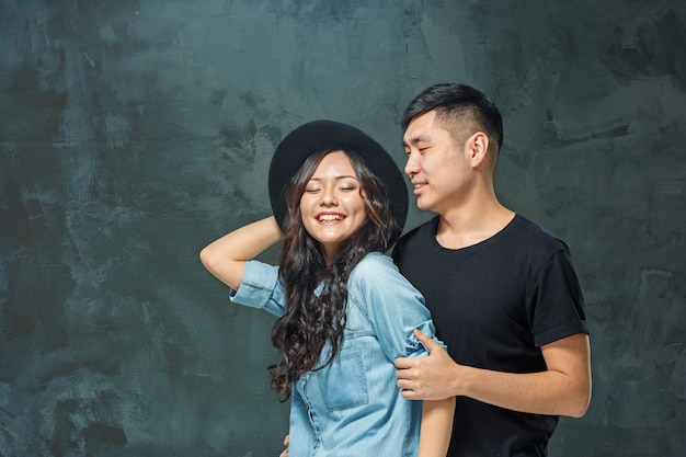 Retrato de casal coreano sorridente em uma parede cinza