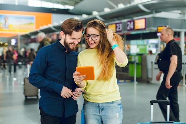 Retrato de casal dançando no aeroporto. ela tem cabelo comprido, óculos, suéter e jeans. ele tem barba, camisa, calças. eles estão procurando no tablet.
