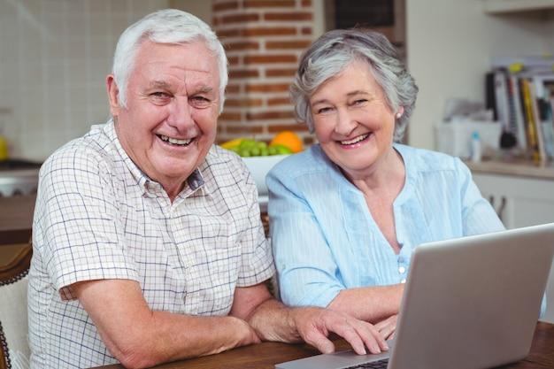 Retrato de casal de aposentados alegres com laptop