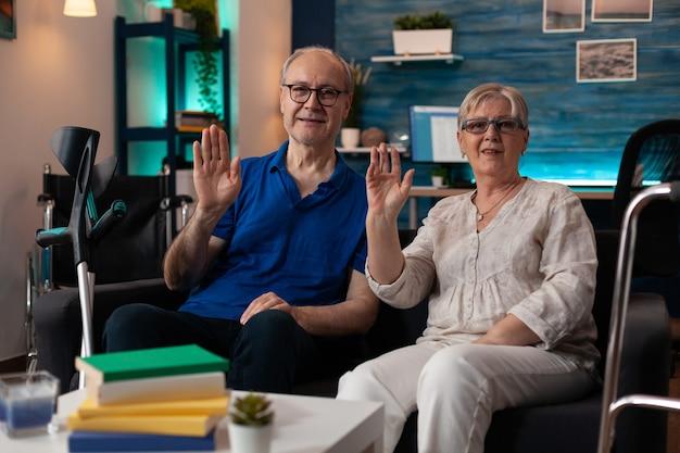 Retrato de casal de aposentados sentado no sofá acenando com as mãos