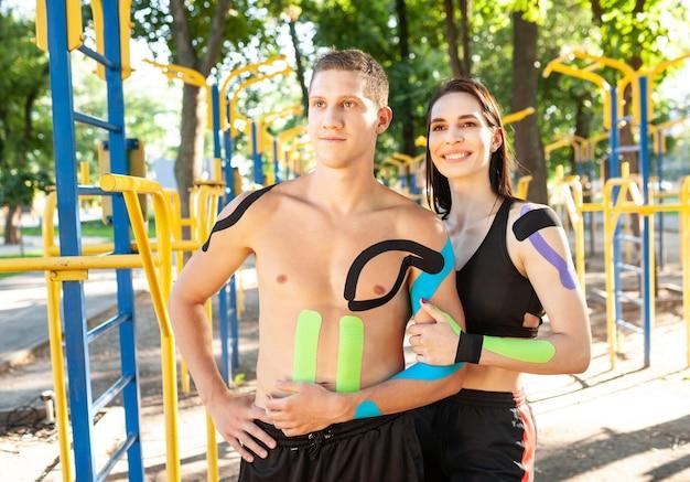 Retrato de casal de atletas profissionais caucasianos e um homem bonito e uma mulher morena com fitas cinesiológicas nos corpos